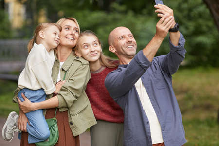 Waist up portrait of modern happy family with two daughters taking selfie photo outdoors while enjoying walk in green park
