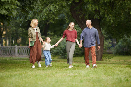 Full length portrait of modern carefree family with two kids holding hands while walking towards camera on green grass outdoors, copy space Foto de archivo