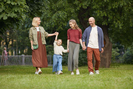 Full length portrait of carefree family with two kids holding hands while walking towards camera on green grass outdoors, copy space Foto de archivo
