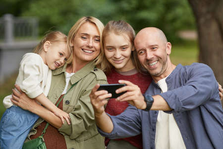 Waist up portrait of modern happy family with two daughters taking selfie outdoors via smartphone while enjoying walk in green park