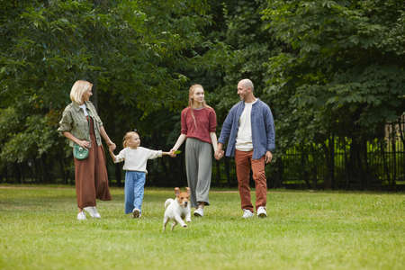 Wide angle portrait of carefree family with two kids and pet dog holding hands while walking towards camera on green grass outdoors, copy space Foto de archivo