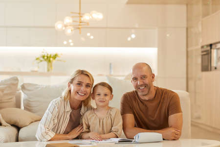 Warm-toned portrait of happy young family looking at camera and smiling while helping cute little girl drawing on studying at home, copy space