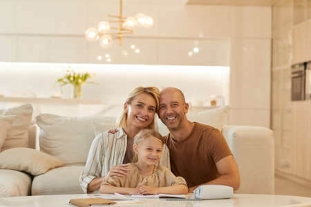 Warm-toned portrait of happy family looking at camera and smiling while helping cute little girl drawing on studying at home, copy space