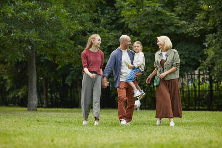 Full length portrait of carefree family with two daughters standing on green grass outdoors while enjoying walk in park together, copy space