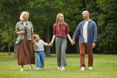 Full length portrait of modern family with two kids holding hands while walking towards camera on green grass outdoors, copy space