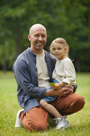 Vertical full length portrait of happy mature father holding cute little daughter and looking at camera while sitting on green grass outdoors enjoying family time in park, copy space