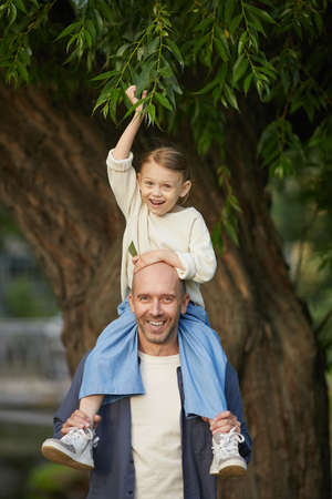 Vertical portrait of cute little girl laughing happily while sitting on dads shoulders and enjoying walk in park, both looking at camera