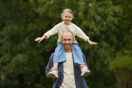 Portrait of cute girl sitting on dads shoulders and having fun while enjoying walk in park, both smiling at camera, copy space