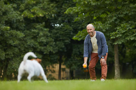 Full length portrait of smiling mature man playing with dog in park, throwing ball on green grass and having fun with pet, copy space