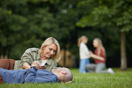 Portrait of loving adult couple laying on green grass in park and enjoying time together outdoors, copy space