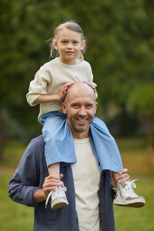 Vertical portrait of cute girl sitting on dads shoulders and enjoying walk in park, both smiling at camera