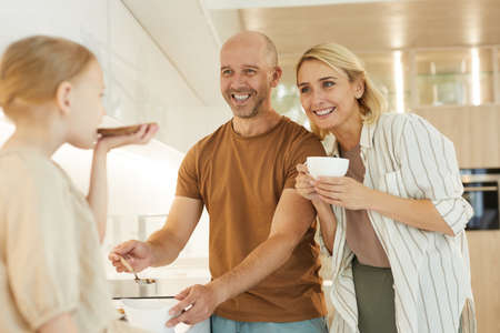 Warm-toned waist up portrait of happy parents looking at cute little girl easing healthy breakfast in modern kitchen interior