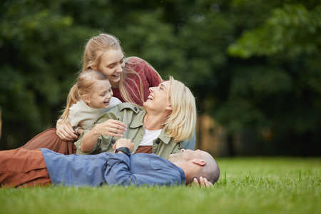 Portrait of happy modern family lying on green grass in park while having fun together outdoors, copy space Foto de archivo