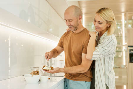 Warm-toned waist up portrait of happy adult couple cooking healthy breakfast together while standing in modern kitchen interior, copy space Foto de archivo