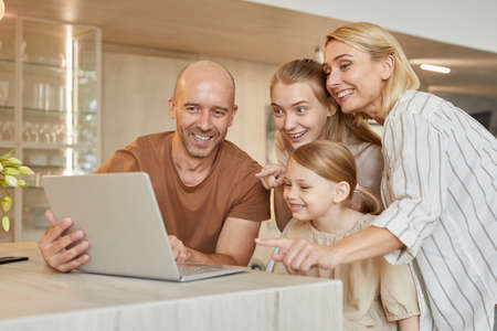 Warm-toned portrait of happy modern family using laptop together while speaking by video chat with relatives in cozy home interior, copy space