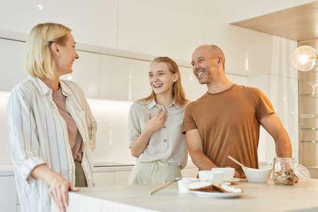 Warm-toned waist up portrait of modern family laughing happily while enjoying breakfast together standing by table in minimal kitchen interior, copy space