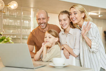 Warm-toned portrait of modern happy family waving at camera while speaking by video chat with relatives, copy space Foto de archivo