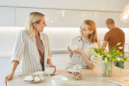 Warm-toned portrait of modern happy family in kitchen, focus on smiling mother talking to teenage daughter while enjoying breakfast, copy space
