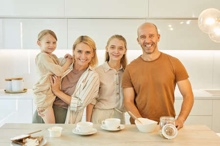 Warm-toned waist up portrait of modern happy family looking at camera while enjoying breakfast together standing by table in minimal kitchen interior, copy space