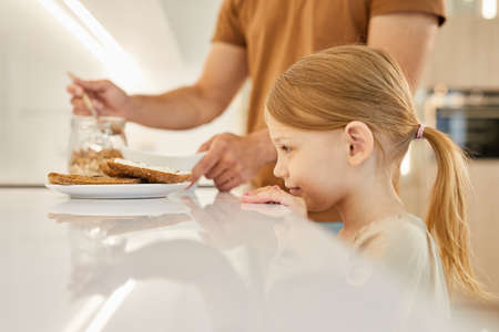 Side view portrait of cute little girl looking at tasty sandwiches while waiting for breakfast in kitchen, copy space