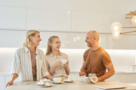 Warm-toned waist up portrait of modern happy family enjoying breakfast together while standing by table in minimal kitchen interior, copy space Foto de archivo