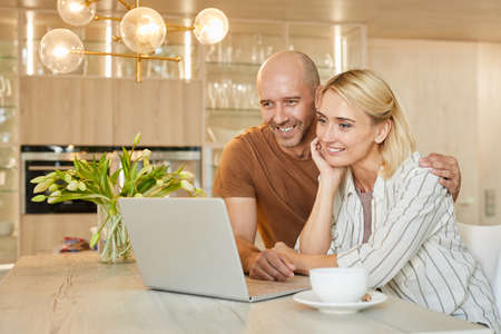 Warm-toned portrait of happy adult couple looking at laptop screen and smiling while talking by video chat with family, copy space Foto de archivo