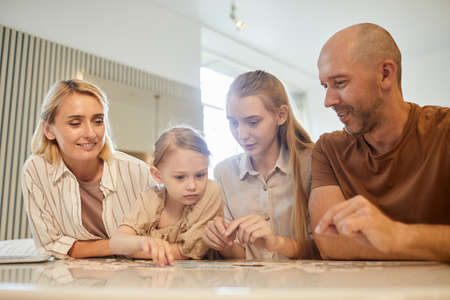 Warm-toned low angle portrait of modern family with two kids solving puzzle together while enjoying time indoors at home, copy space