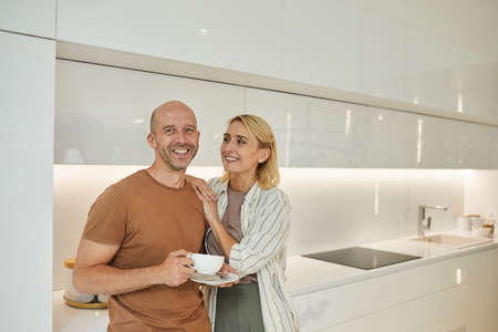 Minimal waist up portrait of loving adult couple smiling while standing in white kitchen interior at home, copy space