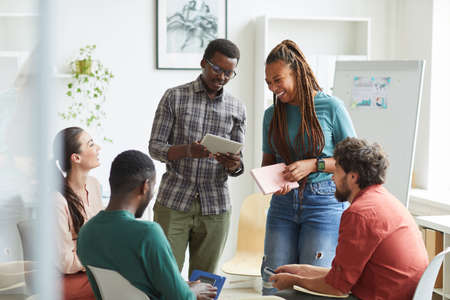 Multi-ethnic group of people sitting in circle while discussing business project in office, focus on smiling African-American woman talking to colleague standing up , copy space