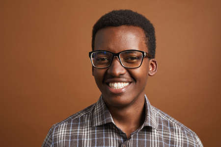 Minimal head and shoulders portrait of young African-American man smiling at camera while standing against brown background in studio, copy space Reklamní fotografie