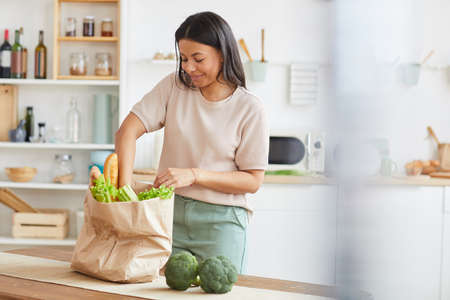 Waist up portrait of elegant mixed-race woman unpacking bags with food while standing in white kitchen interior and smiling, food delivery service, copy space
