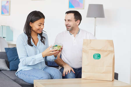 Portrait of smiling man and woman opening food delivery bag while enjoying takeout lunch in office or at home, copy space