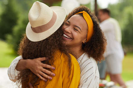 Portrait of young African-American woman hugging friend and smiling cheerfully while enjoying outdoor party in Summer