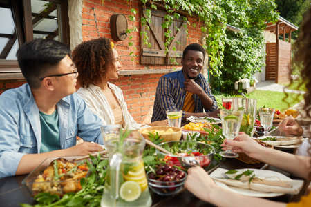 Portrait of multi-ethnic group of friends enjoying dinner together outdoors while sitting at table on open terrace, focus on smiling African-American man sharing stories, copy space