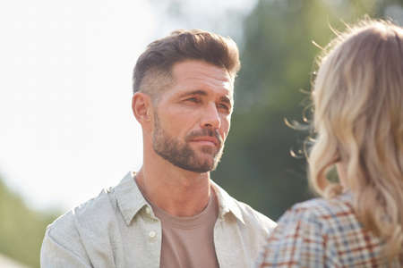 Head and shoulders portrait of handsome adult man looking at girlfriend while enjoying romantic date outdoors in sunlight, copy space