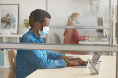 Side view portrait of young African-American man wearing mask and using laptop while sitting at desk in cubicle at post pandemic office, copy space