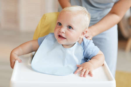 Unrecognizable woman getting her little kid into his bib while he is sitting on high chair, copy space