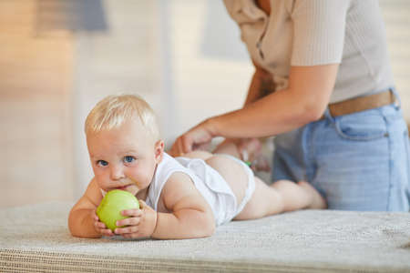 Modern mother changing clothes of her little baby son while he is biting green apple Foto de archivo