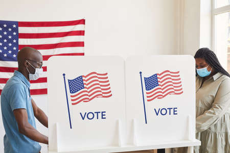Side view portrait of two African-American people wearing masks standing in voting booths opposite each other on post-pandemic election day, copy space