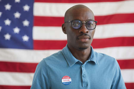 Head and shoulders portrait of bald African-American man with VOTE sticker looking at camera while standing against American flag on election day, copy space 写真素材