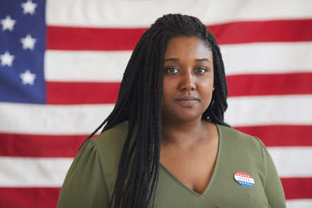 Head and shoulders portrait of young African-American woman with VOTE sticker looking at camera while standing against American flag on election day, copy space