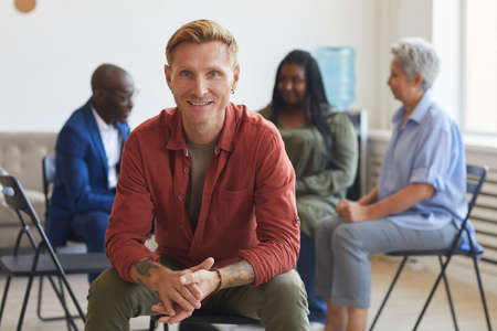 Portrait of smiling tattooed man looking at camera during support group meeting with people in background, copy space