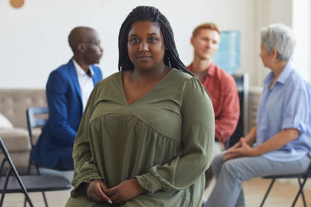 Portrait of young African-American woman looking at camera during support group meeting with people sitting in circle in background, copy space