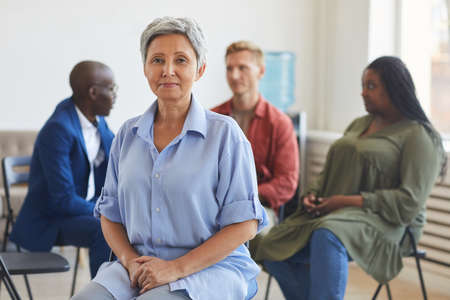 Portrait of smiling mature woman looking at camera during support group meeting with people sitting in circle, copy space 写真素材