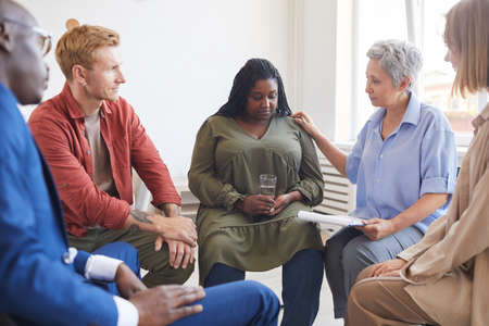 Portrait of young African-American woman sharing struggles during support group meeting with people siting in circle and comforting her