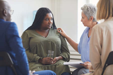 Portrait of sad African-American woman listening to psychologist during support group meeting with people siting in circle and comforting her 写真素材