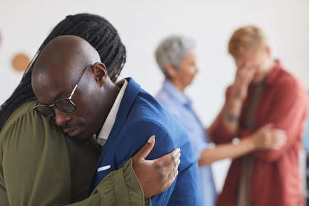 Side view at two African-American people embracing during support group meeting, helping each other with stress, anxiety and grief, copy space