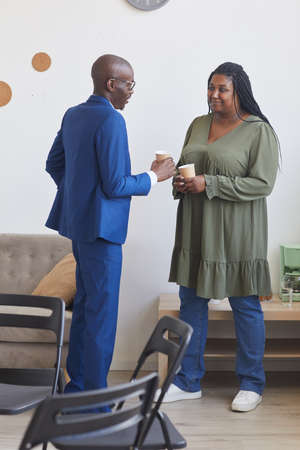 Vertical full length portrait of two African-American people talking during coffee break in support group meeting 写真素材