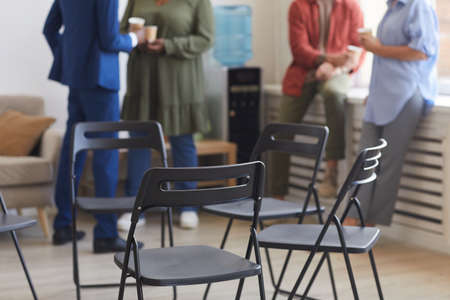 Cropped shot of empty chairs in circle during support group meeting with people chatting in background, copy space