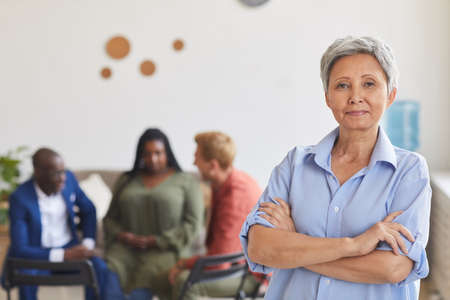 Waist up portrait of modern mature woman posing confidently and looking at camera with people sitting in circle in background, group leader concept, copy space 写真素材